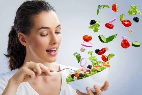 Contre le coronavirus, une bonne santé que se prépare cette jeune dame souriante tenant un bol de légumes et fruits tranchés, colorés, fort appétissants.