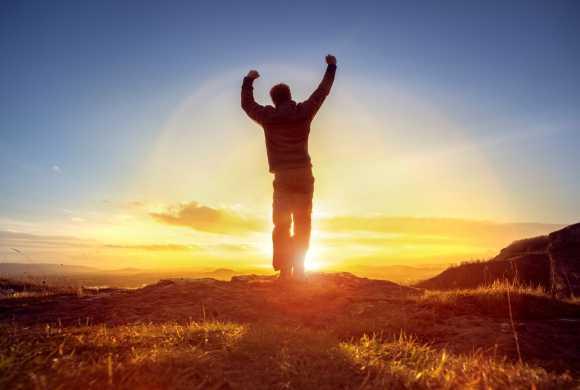 Fort contre le coronavirus, un homme debout rayonnant de sante exulte devant le soleil radieux.