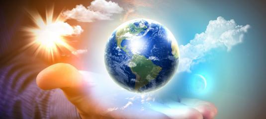 Pour la paix dans le monde, une main d'homme tient la Terre entourée d'une douce lumière bleutée avec quelques nuages blancs.